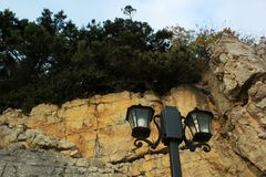Green trees, nature of the Crimea,a large rock and a street lamp, a quay and a stone coast, rocks on the seashore, a tall black p. A large rock and a street lamp stock photo