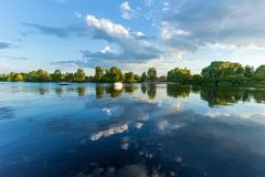 Green trees reflect in the water of the river. In the sky there are dramatic clouds Royalty Free Stock Photos