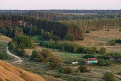 Green trees, road and meadows viewed from high hill in sunset li Stock Image