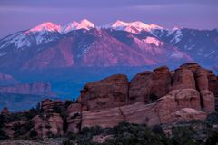 Green Trees and Rock Formation Overlooking Snow Coated Mountain Ranges at Daytime Stock Images