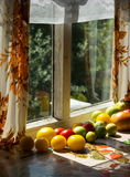 Green trees seen through the old window. tomatoes lie near a window Stock Photos