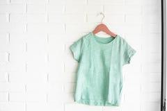Green tshirt hanging on an orange hanger Royalty Free Stock Image