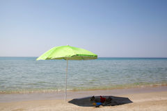 Green umbrella on the beach Royalty Free Stock Photo