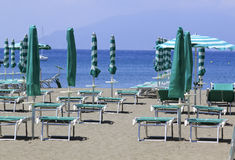 Green umbrellas. A detail of a beach with closed and opened umbrellas in italian riviera waiting for summer Stock Photos