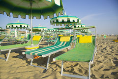Green umbrellas and chaise lounges on the beach of Rimini in Ita Royalty Free Stock Images