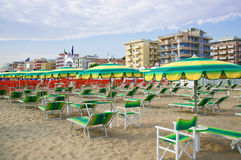 Green umbrellas and chaise lounges on the beach of Rimini in Italy Stock Photo