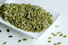 Raw unshelled pumpkin seeds in plate. Royalty Free Stock Images