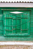 Green unusual wooden window in a painted wall Royalty Free Stock Photography