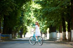 Green urban plantings. Female rides on bike alone at road. Green urban plantings. Female rides on retro bike alone at road on a summer day. The girl is dressed royalty free stock image
