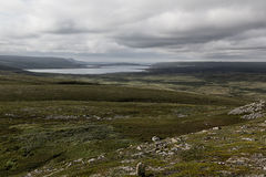 Green valley and lake in cloudy weather, highlands. Stock Image