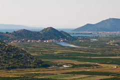 Green valley with sea and hills in distance. Beautiful Neretva valley in southern Croatia with crop fields in foreground and hills and sea in background Stock Images