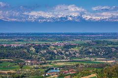 Green valley and snowy mountains in Piedmont, Italy. Royalty Free Stock Image