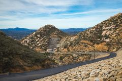 Green Valley Truck Trail. Stunning elevated view from Green Valley Truck Trail of a boulder-covered dam with mountains in the distance, Blue Sky Ecological royalty free stock image