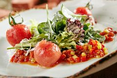 Green Vegan Salad. With Baked Sweet Pepper, Red Cherry Tomatoes and Lettuce Leaves on Natural Vintage Ceramic Plate. Beautifully Served Cooked Vegetables with royalty free stock photography