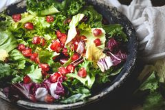 Green vegan salad in bowl with endive, arugula, mixed lettuces and pomegranate. Dieting, vegan food concept stock photography