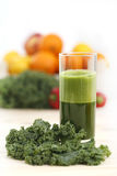Green vegetable juice in a tall glass with a leaf of kale Stock Photo