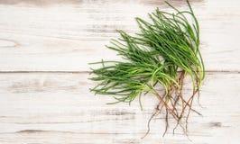 Green vegetable monks beard wooden kitchen table Stock Image