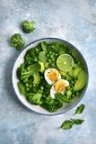 Green vegetable salad with avocado, broccoli, pea and boiled eggs on a light blue slate, stone or concrete background.Top view stock image