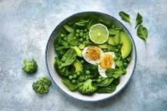 Green vegetable salad with avocado, broccoli, pea and boiled eggs on a light blue slate, stone or concrete background.Top view stock images