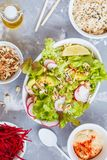 Green vegetable salad with rice, hummus and sprouts. Gray background, top view. Healthy detox vegan food concept Royalty Free Stock Photography