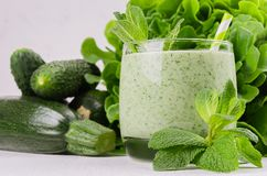 Green vegetable smoothie in glass with deep green vegetables and straw, mint, closeup. Soft white wooden board background stock photo