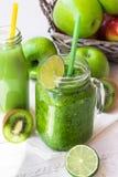 Green vegetable smoothie in jar mug, bottle with fresh fruit juice, apples, citrus, kiwi, on wood table outdoors Stock Images