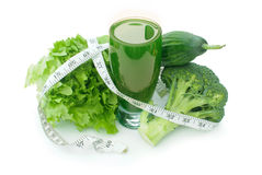 Green vegetable smoothie. Tape measure wrapped around a refreshing green vegetable juice Royalty Free Stock Image
