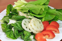 Green Vegetables. Fresh green vegetables: choy-sum, bok-choy slice lotus roots, slice tomato and mushroom in a plate Royalty Free Stock Image