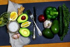 Green vegetables avocados, pepper, lemon, ginger, garlic, oil, sea salt, rucola salad, cucumber, fork and knife on a shale board, stock photo