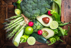 Green vegetables background. Mix of green fresh vegetables on rustic wood background.Green peppers cabbage celery avocado asparagus cucumber radishes broccoli Stock Photos