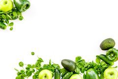 Green vegetables background. Shiny bell pepper, cucumber, arugula salad, avocado and fresh apple on white background top. Green vegetables background. Shiny bell Stock Photo
