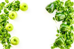 Green vegetables background. Shiny bell pepper, cucumber, arugula salad, avocado and fresh apple on white background top. Green vegetables background. Shiny bell Stock Image