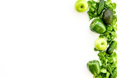 Green vegetables background. Shiny bell pepper, cucumber, arugula salad, avocado and fresh apple on white background top. Green vegetables background. Shiny bell Royalty Free Stock Photos
