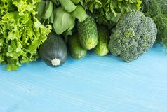 Green vegetables on a blue wooden background. Parsley, spinach, cucumber, broccoli, dill and zucchini. Top view. Green vegetables. At border of image with copy Stock Image