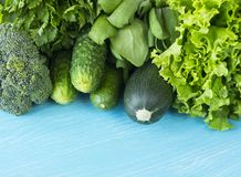 Green vegetables on a blue wooden background. Parsley, spinach, cucumber, broccoli, dill and zucchini. Top view. Green vegetables. At border of image with copy Stock Images