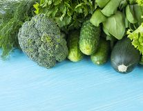 Green vegetables on a blue wooden background. Parsley, spinach, cucumber, broccoli, dill and zucchini. Top view. Green vegetables. At border of image with copy Stock Photography