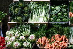 Green vegetables and carrots on a market stall Stock Photos