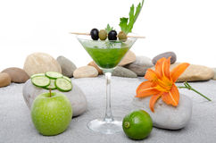 Green vegetables cocktail in a environment of sand and pebble st Royalty Free Stock Images