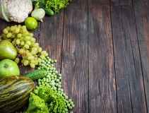 Green vegetables and fruits on dark wooden background.  Stock Image