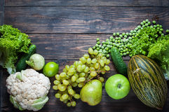 Green vegetables and fruits on dark wooden background. Top view. Royalty Free Stock Images