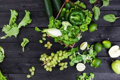 Green vegetables, fruits and herbs on black wooden table. Top view royalty free stock photo