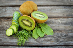 Green vegetables and fruits: kiwi, cucumber, dill, sorrel on wooden background. Royalty Free Stock Photo