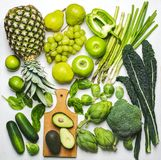 Green vegetables and fruits on a white background. Fresh organic produce. Healthy food. Top view royalty free stock photos