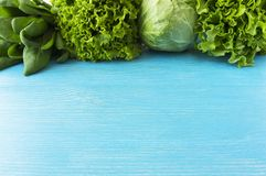 Green vegetables. Green vegetable on blue wooden background. Spinach, cabbage and lettuce. Top view. Vegetables at border of image. With copy space for text royalty free stock images