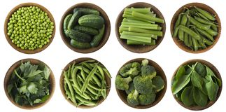 Green vegetables isolated on a white background. Brocoli, green peas, cucumbers and leaves parsley, celery, spinach in wooden bowl Stock Photos