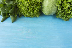 Green vegetables, lettuce and herbs at border of image with copy. Space for text. Top view. Cabbage, spinach, dill and lettuce. Green vegetables on a blue Stock Images