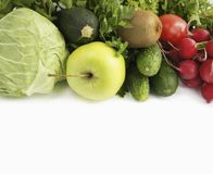 Green vegetables, lettuce, herbs and fruits. At border of image with copy space for text. Cabbage, zucchini, cucumbers, radish, tomatoes, kiwi, spinach, parsley Royalty Free Stock Photo