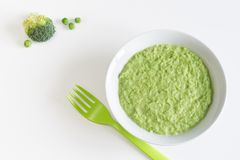 Green vegetables puree made from peas and broccoli. Bowl of pureed green vegetables for baby on white background Stock Photography