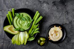 Green vegetables snack board with herb hummus or pesto dip. Healthy raw summer appetizer platter. stock images