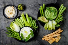 Green vegetables snack board with various dips. Yogurt sauce or labneh, hummus, herb hummus or pesto with crackers, grissini bread stock photos